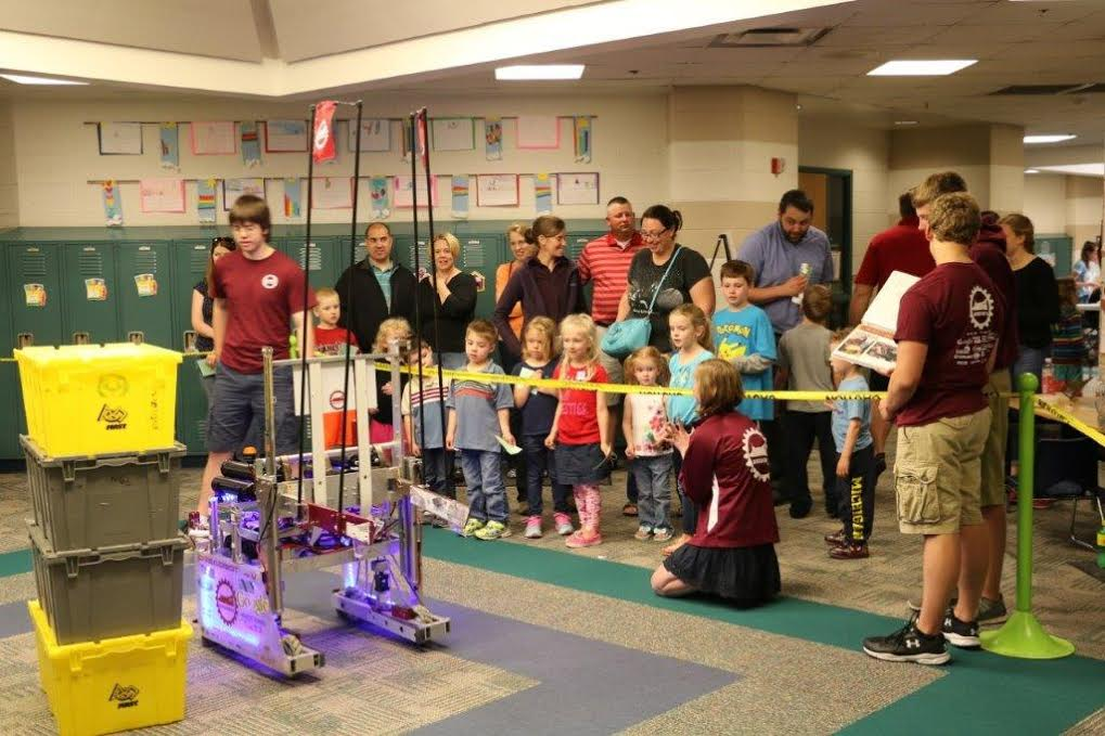 group of young kids looking at robot