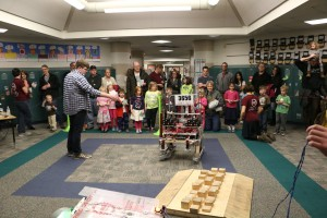 kids and parents watch a robot demo