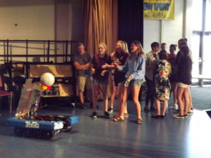 A group of girls interacting with a robot.
