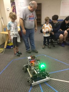 little boy driving robot while others watch