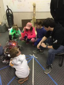 a group of young kids get a up close look at the robot