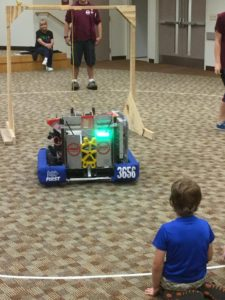 A child looks at our robot.