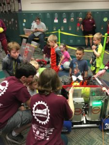 excited young students looking at a robot