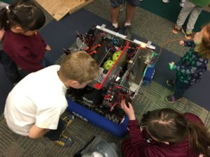 kids looking closely at our robot