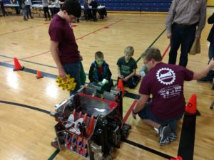three boys get a up close look at the robot