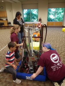 a couple young kids looking at our robot